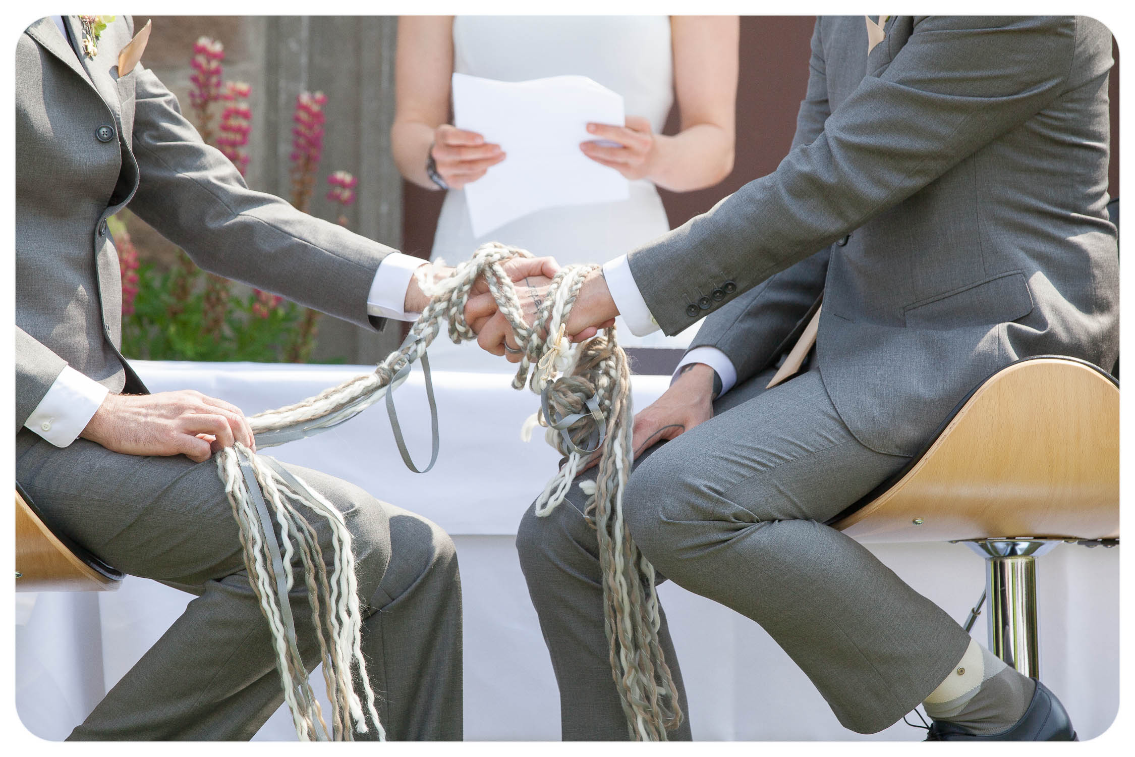 Photo of two people wearing grey suits. Their left hands are clasped and wrapped in a grey, white and taupe plaited cord. It's a handfasting ceremony.