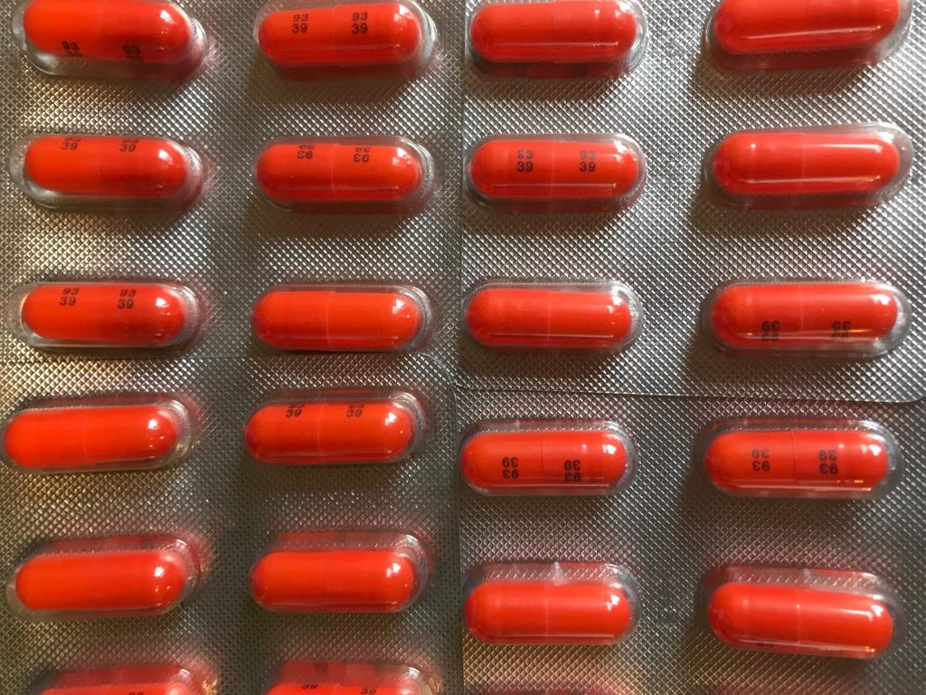 Image description: rows of orange pills in blister packs